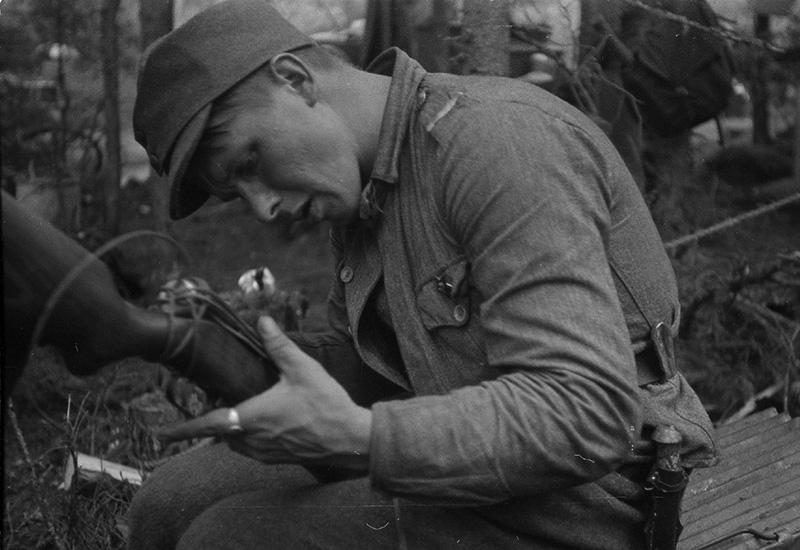 Капрал финской армии с помощью подручных средств ремонтирует трофейный советский пистолет-пулемет ППД-34