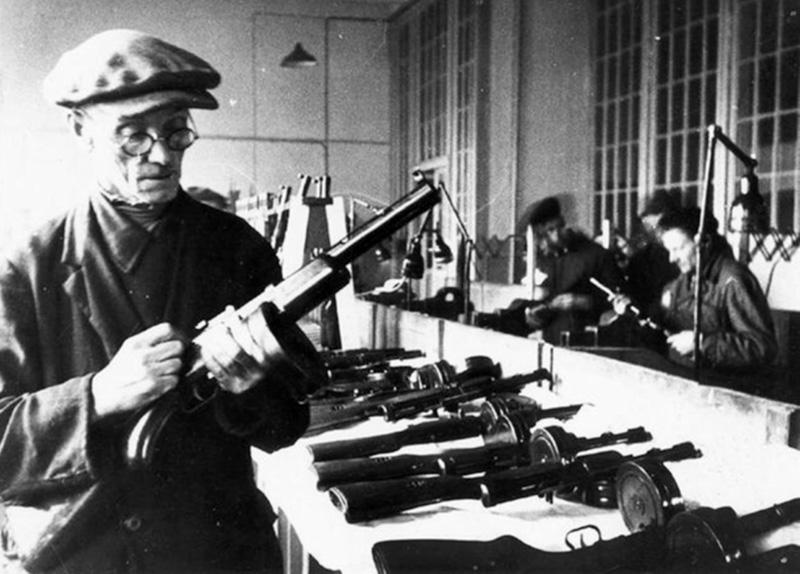 Контрольный мастер осматривает готовые пистолеты-пулеметы перед отправкой на фронт